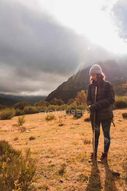 Jeune femme en chapeau et veste de ski avec sac à dos et bâton de marche debout sur le terrain près de la montagne dans les nuages avec soleil à Isoba, Castille et Léon, Espagne — Photo de stock