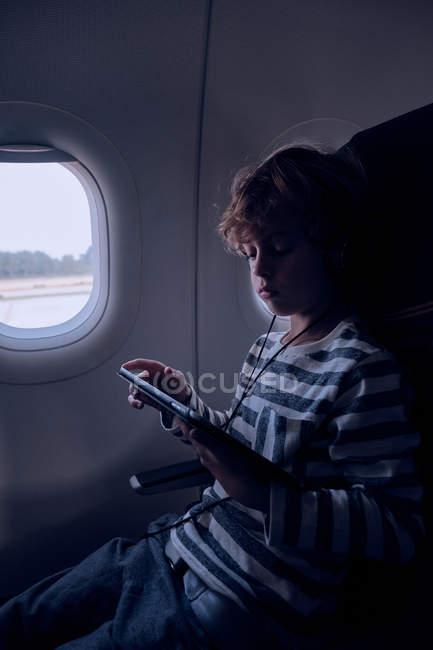 Привабливий хлопчик у повсякденному спорядженні дивиться фільм на сучасній дощечці, сидячи біля вікна в темній хатині сучасного літака. — стокове фото