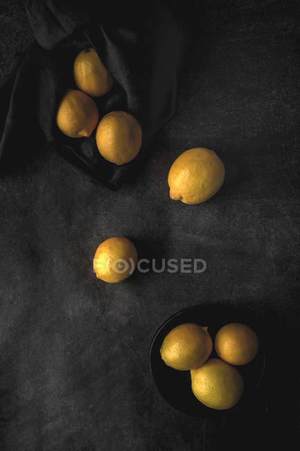 Frische reife Zitronen auf dunklem Hintergrund verstreut — Stockfoto