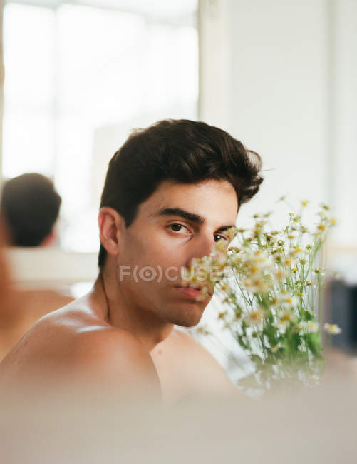 Side view of young shirtless guy with fresh white flowers in hands looking at camera on blurred background — Stock Photo