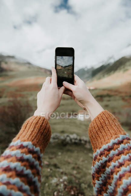 Crop hands of lady with mobile phone shooting picturesque view of valley with wonderful mountains and cloudy heaven in Pyrenees — Fotografia de Stock