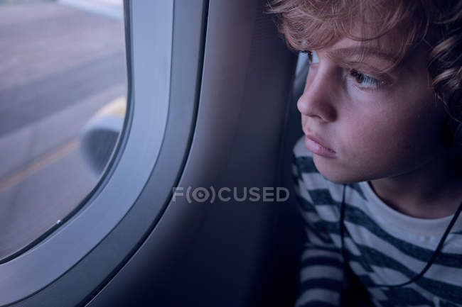 Cute boy with headphones in plane — Stock Photo
