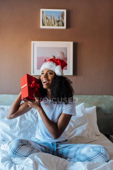 Жінка з капелюхом з Санта Клауса з подарунком під час хрещення сидить на ліжку вдома посміхаючись — стокове фото