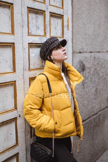 Dreamy young woman in trendy outfit looking away while standing near weathered wall on city street — Stock Photo