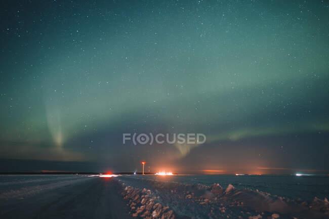 Величественный полярный свет, сияющий в ночном небе над снежной дорогой в сельской местности Арктики — стоковое фото
