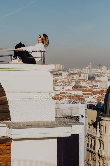 Side view of young stylish lady in casual wear and sunglasses leaning on rails on roof and blue sky on cityscape background in Madrid, Spain — Stock Photo