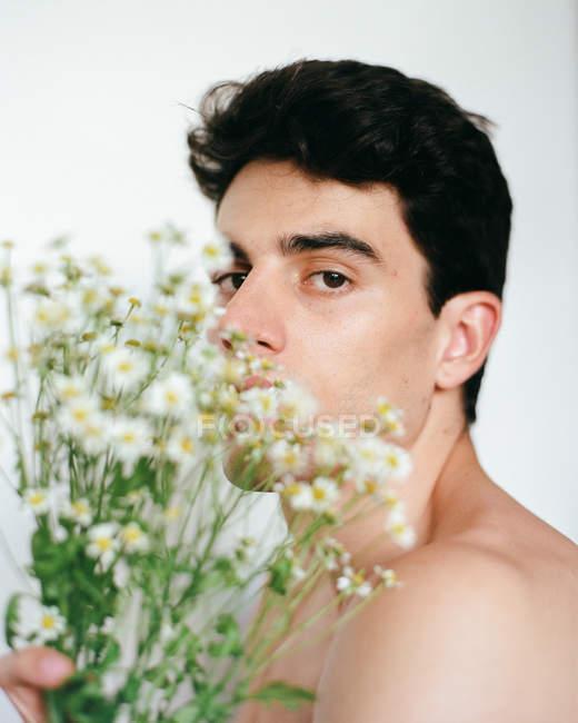 Вигляд молодого безсоромного хлопця з білими квітами в руках, який дивиться на камеру на розмитому фоні. — стокове фото