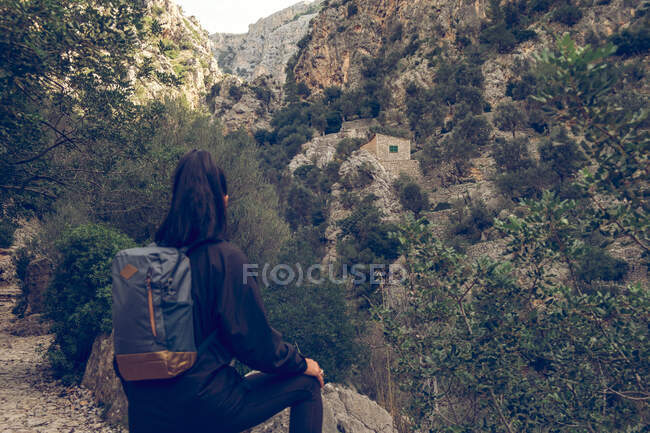На задньому плані жінка з стильним рюкзаком дивиться на чудові скелі в прекрасній сільській місцевості. — стокове фото