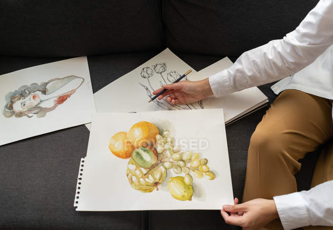 Woman with draws on papers — Stock Photo