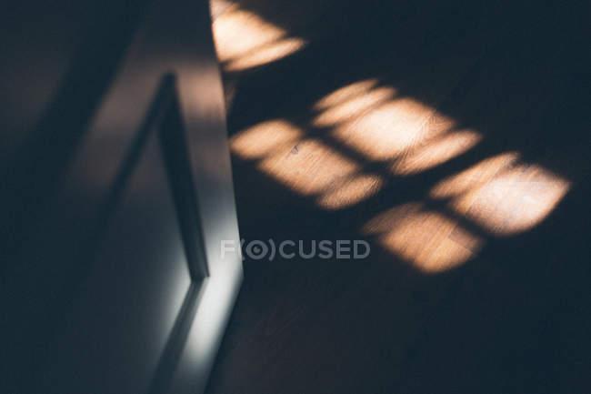 Manchas de luz de la ventana en el suelo de madera cerca de la puerta abierta en habitación oscura - foto de stock
