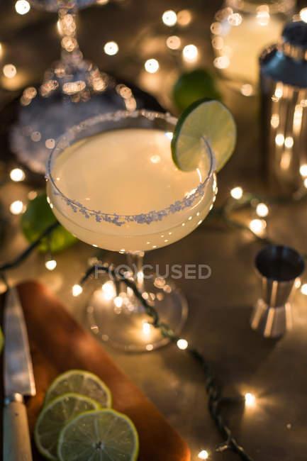 Келих коктейлю Маргарита на стіл з інгредієнтами і вогнями — стокове фото