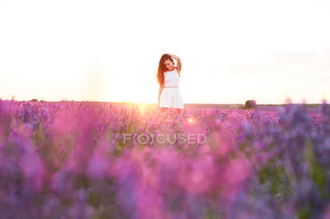 Улыбающаяся молодая женщина в платье в подсветке между фиолетовым лавандовым полем — стоковое фото