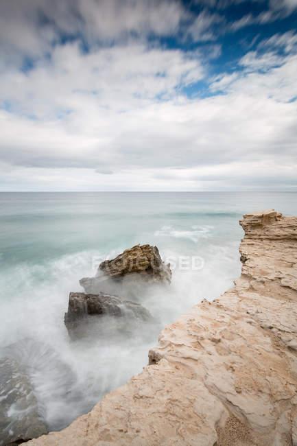 Falaise de pierre rugueuse et mer agitée orageuse sous un ciel nuageux — Photo de stock