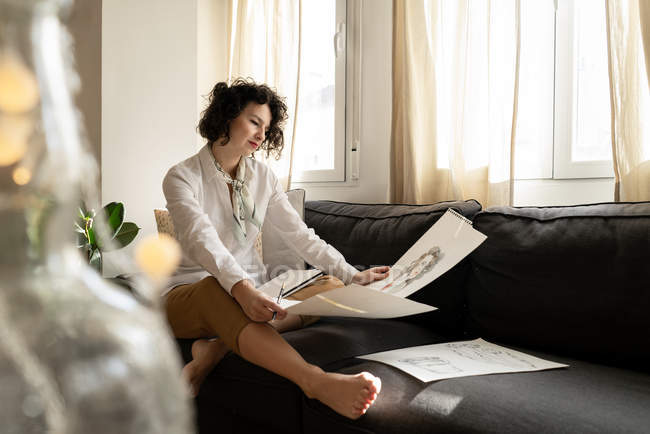 Woman drawing on papers on sofa in room — стокове фото
