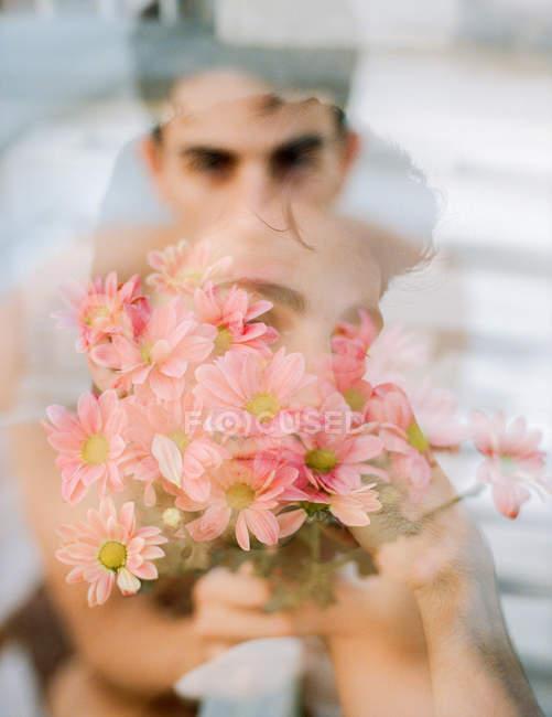 Подвійний вплив брунатного молодика і букету свіжих квітів дивлячись на камеру на розмитому фоні — стокове фото