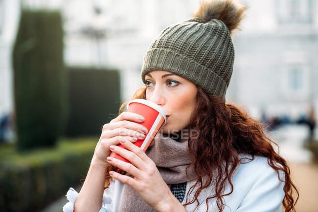 Красивая рыжая женщина пьет кофе на улицах Мадрида зимой — стоковое фото