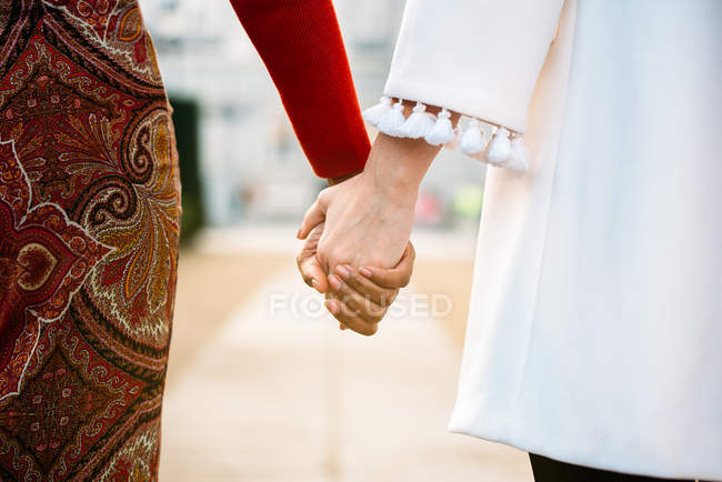 Two unrecognizable interracial women holding hands walking in the streets — Stock Photo