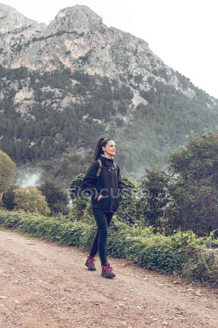 Красуня з рюкзаком посміхається і озирається геть, коли йде по дорозі біля величної гори в величній сільській місцевості. — стокове фото