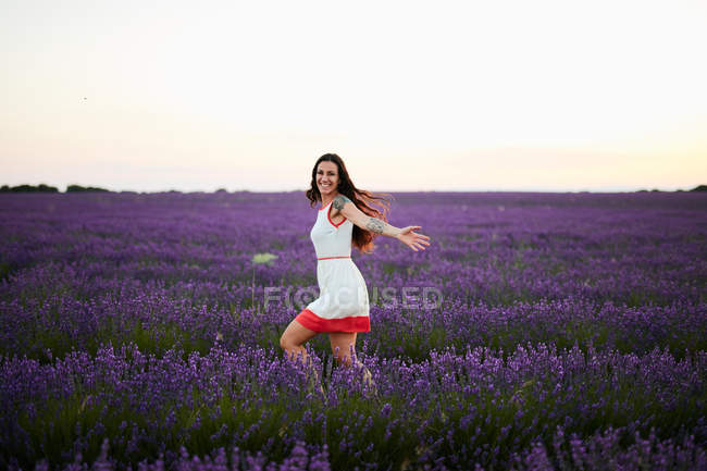 Young woman running between violet lavender field — Stock Photo