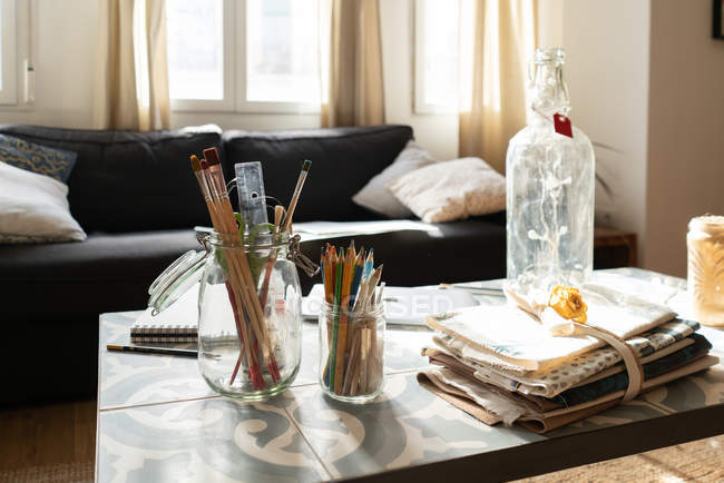 Збирання щіток і олівців у скляних банках біля пляшки і купа матеріалів на низькому столі біля смоли в кімнаті. — стокове фото
