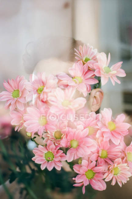 Double exposure of brunette young guy and bouquet of fresh flowers looking at camera on blurred background — Fotografia de Stock