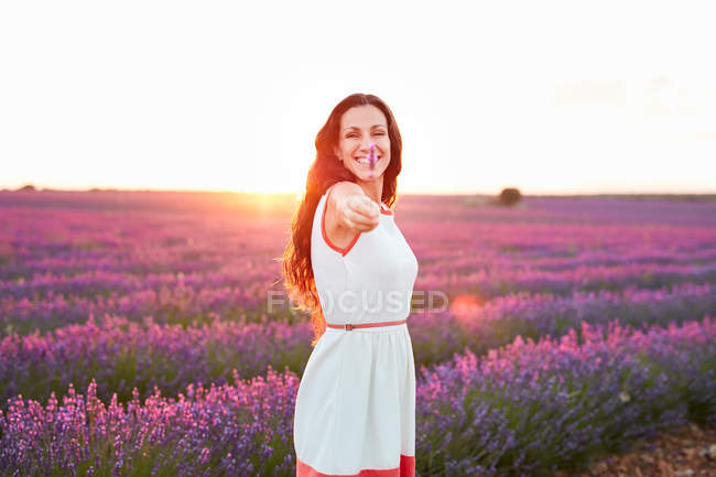 Happy attractive lady with flowers in outstretched arm between beautiful purple blooms on lavender field — Stock Photo
