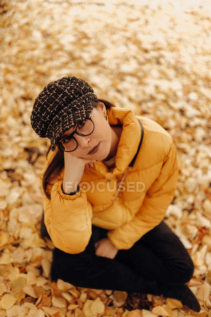 Portrait of young woman in trendy warm clothes looking at camera while sitting on dry autumn leaves in park — Stock Photo