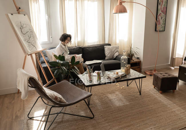 Femme dessin sur papier sur canapé dans la chambre — Photo de stock