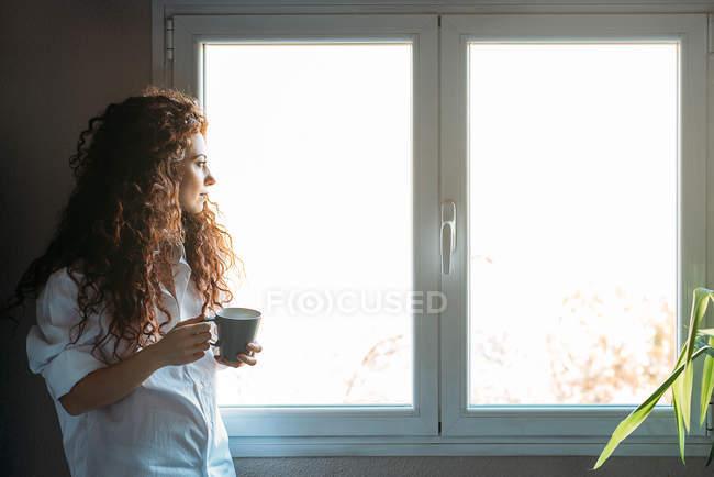 Задумчивая женщина, стоящая у окон с чашкой кофе — стоковое фото