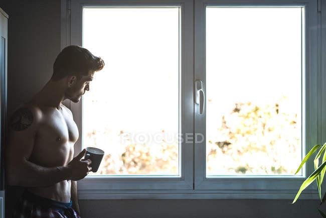 Пильний чоловік стоїть біля вікна з чашкою кави. — стокове фото