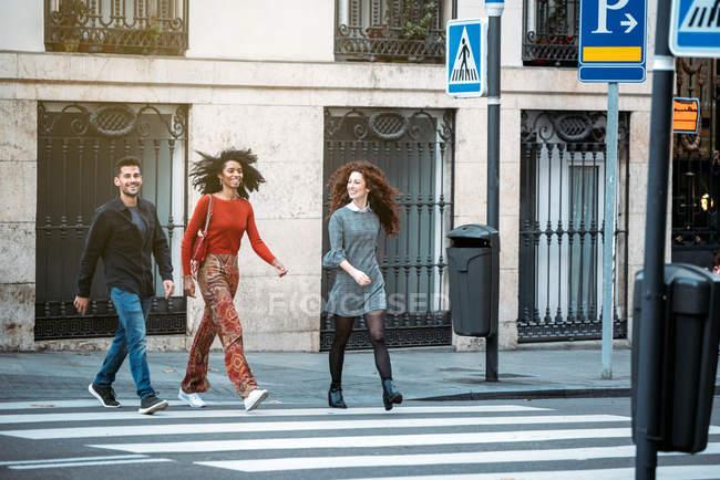 Троє молодих друзів зимою перетинають зебру на вулицях Мадрида. — стокове фото