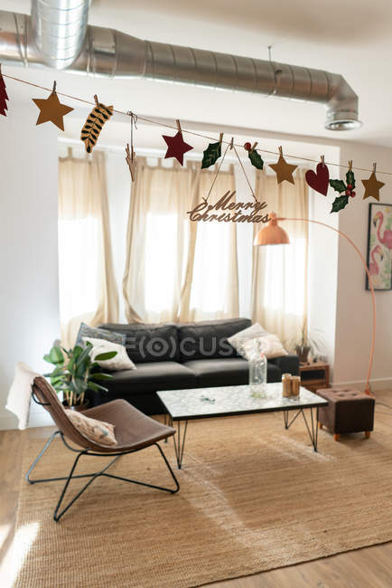 Composition of light room with sofa, chair, table on carpet and Christmas decorations — Stock Photo