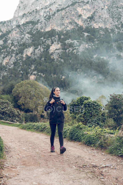 Pretty woman with backpack smiling and looking away while walking along road near magnificent mountain in majestic countryside — Stock Photo