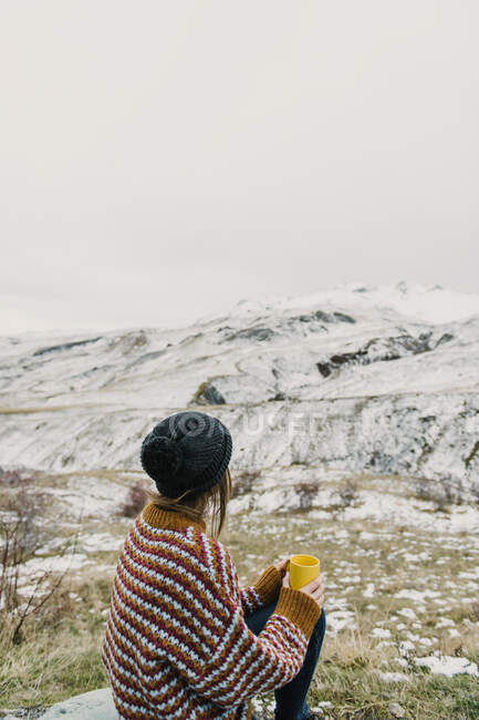 Back view of young lady in sweater and hat holding mug and looking at hills in snow in Pyrenees — Stock Photo