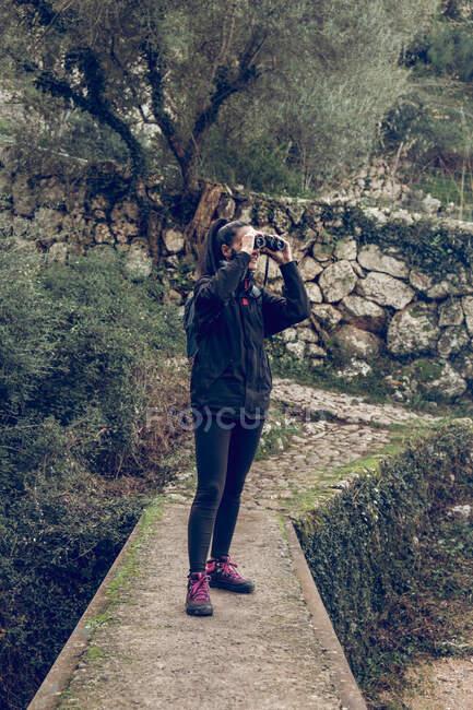 Красива жінка посміхається і дивиться на відстань через сучасні бінокль, стоячи на кам