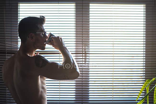 Um homem atencioso junto a uma janela, cego, a beber um café. — Fotografia de Stock
