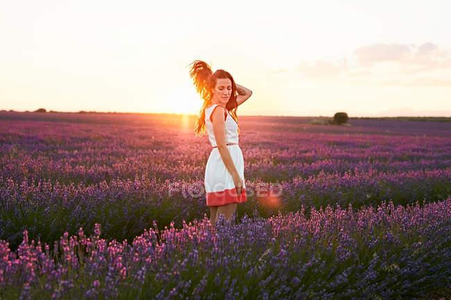 Молода жінка між фіолетовим полем лаванди у підсвічуванням на заході — стокове фото