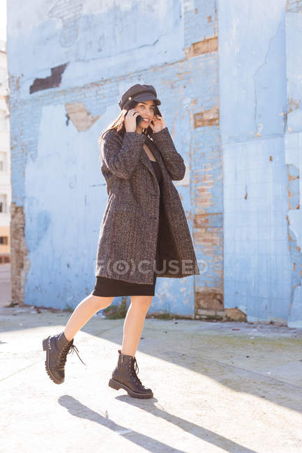 Stylish young woman in coat and cap talking on mobile phone while walking near blue brick wall — Stock Photo
