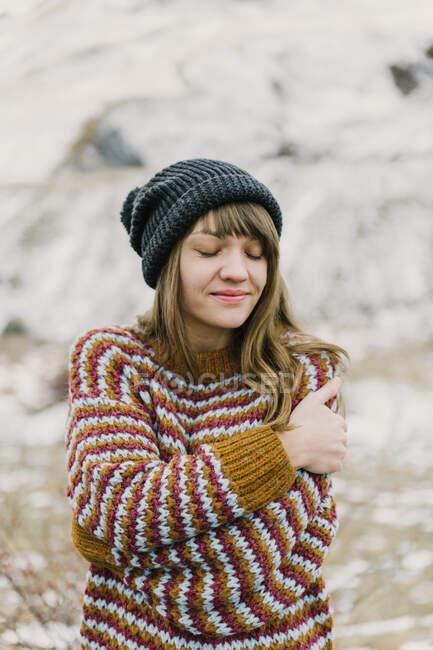 Attraente signorina in maglione e cappello con le mani incrociate vicino collina su sfondo sfocato nei Pirenei — Foto stock