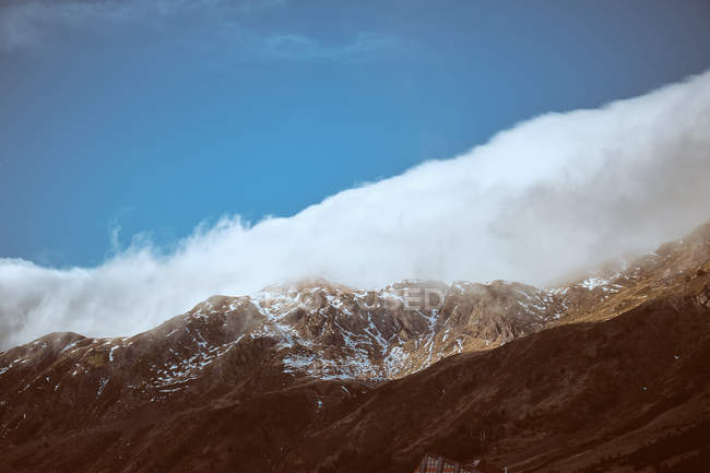 Cloud over majestic mountains under blue sky — Stock Photo
