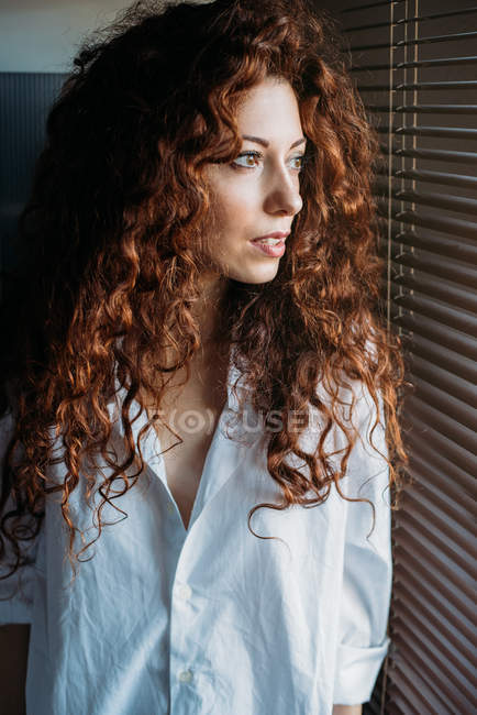 Красивая задумчивая женщина, стоящая у окна вслепую — стоковое фото