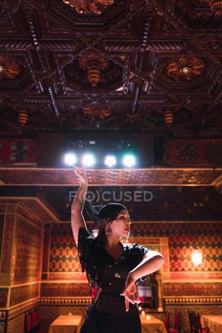 Молодая женщина в платье танцует фламенко на сцене в роскошной восточной комнате, украшенной мозаикой — стоковое фото