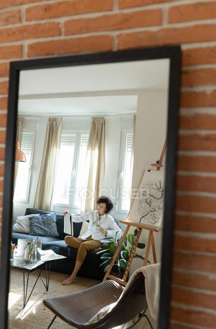 Відбиття молодої жінки, що сидить на паті з листом біля низького столу з пензлями і малює на полотні у світлій кімнаті. — стокове фото