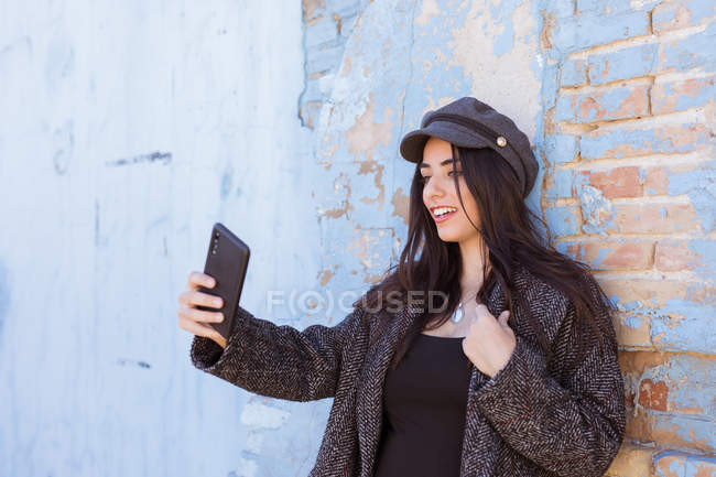 Charming Hispanic lady taking selfie with mobile phone in front of shabby wall — Stock Photo