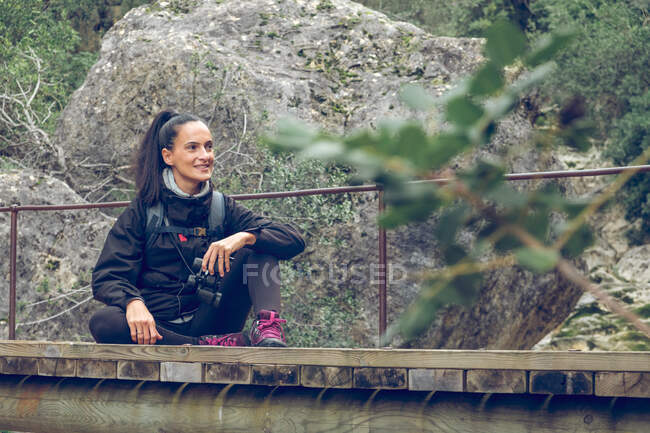 Beautiful female smiling and looking away and holding binoculars while sitting on small bridge over calm stream with clean water in wonderful park in Soller, Spain — Stock Photo