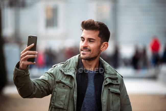 Jovem no celular e andando em madrid durante o inverno — Fotografia de Stock