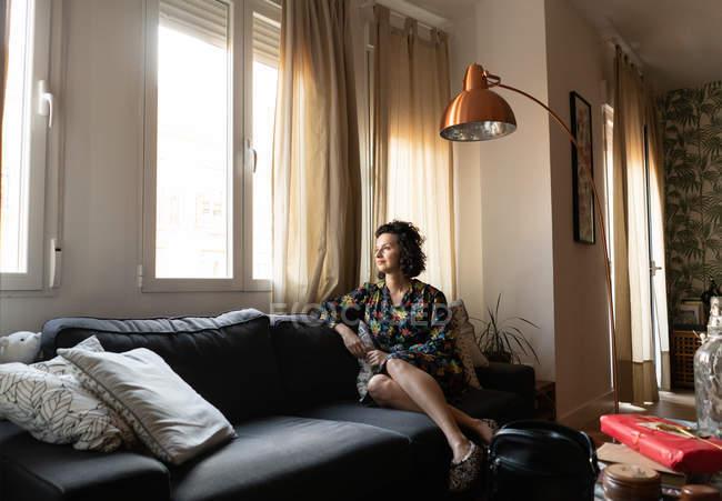Молода приваблива жінка в сукні сидить на кареті в квартирі і дивиться через вікно. — стокове фото