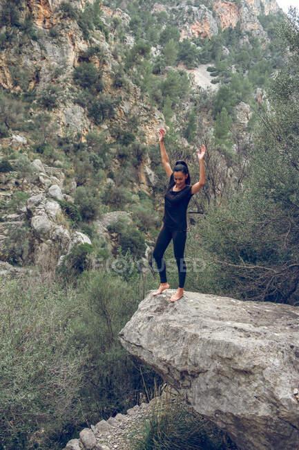 Attraente femmina in abito casual sorridente con le braccia sul bordo della pietra grezza vicino meravigliosa montagna nel bellissimo parco — Foto stock