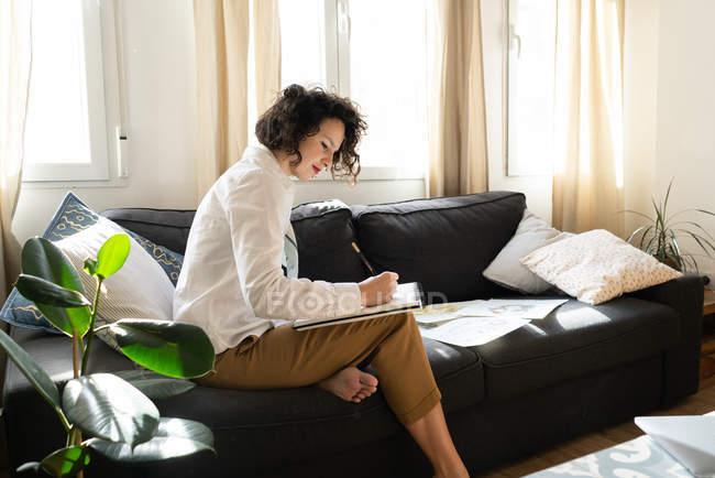 Жінка пише на папері на дивані в кімнаті. — стокове фото