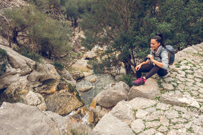 Beautiful woman smiling and looking at distance through modern binoculars while sitting on stone path over calm stream in park Soller, Spain — Stock Photo